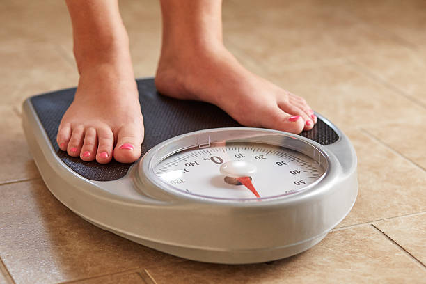 female feet on weight scale - weights stock photos and pictures