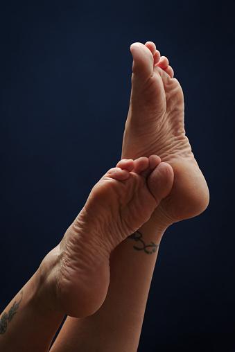 Female Feet Soles On Dark Blue Background 23 - Fotografie stock e altre immagini di Adulto