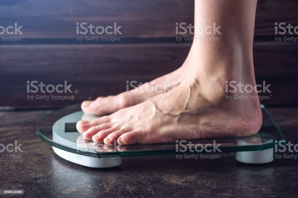 Female feet standing on electronic scales for weight control on dark background. Concept of sports training, diets stock photo