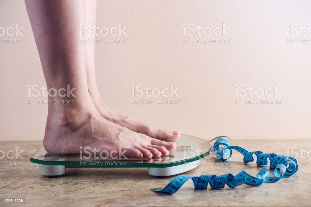 Female feet standing on electronic scales for weight control on light background. Concept of sports training, diets stock photo