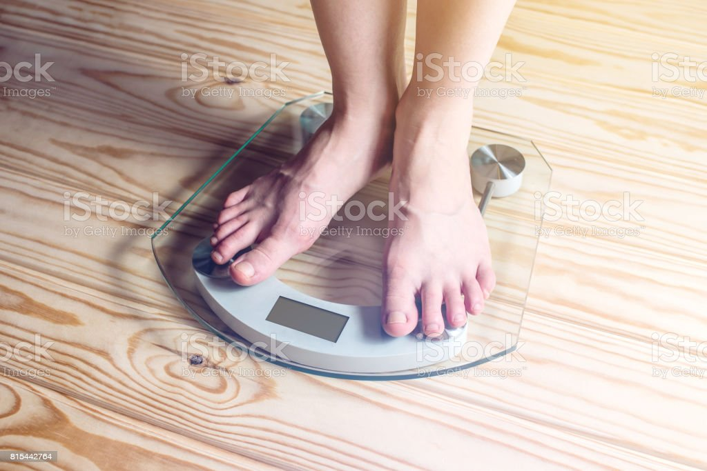 Female feet standing on electronic scales for weight control stock photo