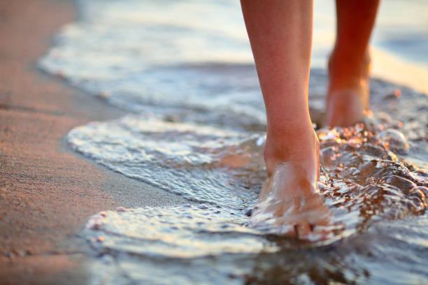 female feet step on the sea wave - scalzo foto e immagini stock
