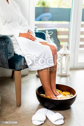 Woman having her feet in a bowl of water with fruit slices.