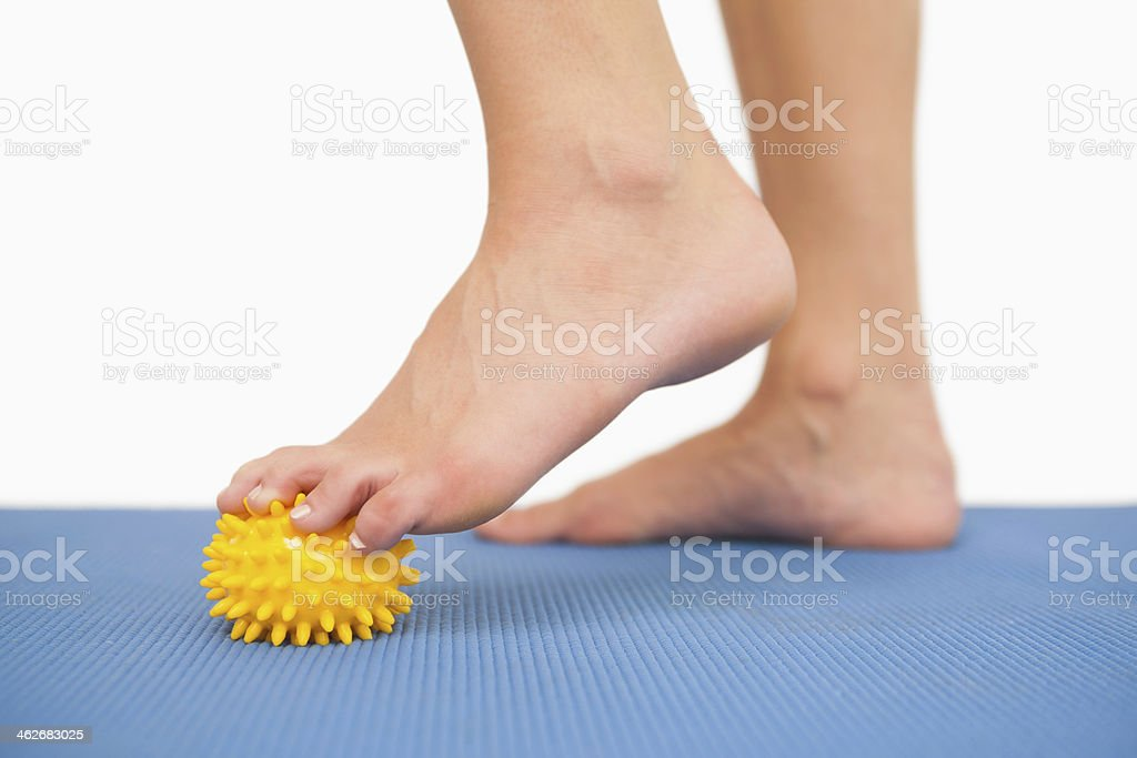 Female feet touching yellow massage ball stock photo