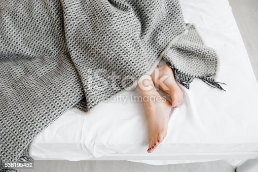 istock Female feet under blanket flat lay 538195452