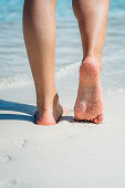 Closeup of woman's feet walking down a tropical sandy beach.