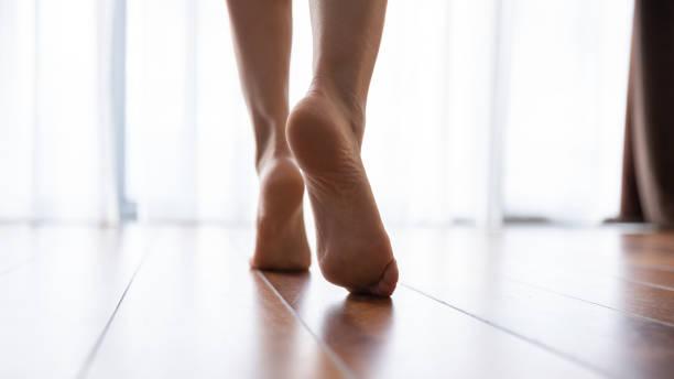 female feet walking on warm heated floor close up view - scalzo foto e immagini stock