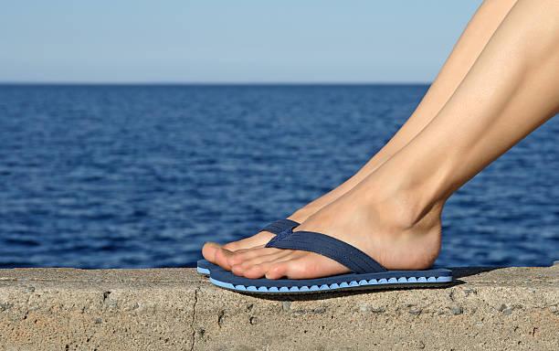 weibliche füße mit blauen flip-flops - salzwasser sandalen stock-fotos und bilder