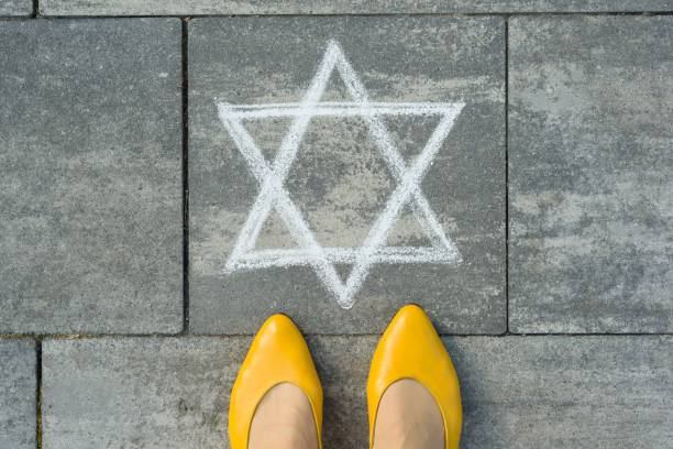 Female feet with abstract image of a six-pointed star, written on grey sidewalk. stock photo