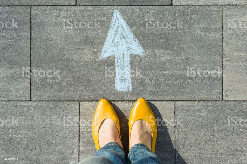 Femmes pieds avec flèche peint sur l'asphalte. photo libre de droits