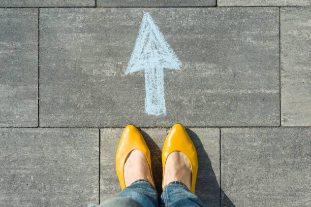 Female feet with arrow painted on the asphalt. stock photo