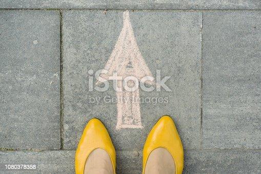 Female feet with arrow painted on the grey sidewalk.