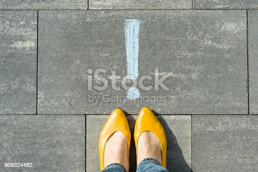 istock Female feet with exclamation point, symbol of attention drawn on the asphalt 959324482
