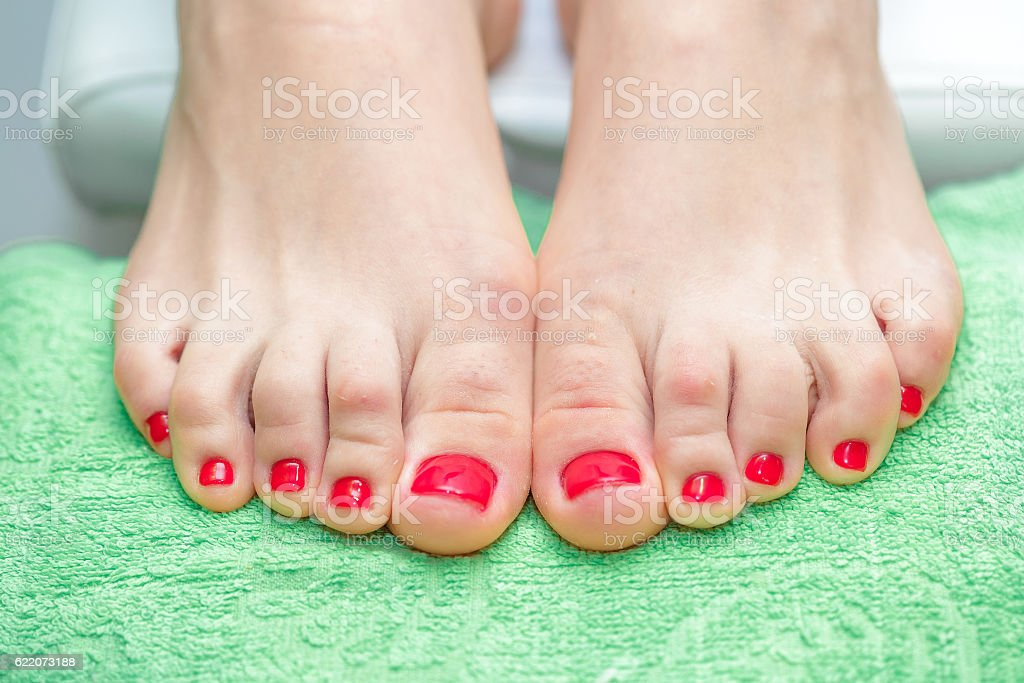 female feet with red nail Polish stock photo