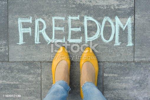 istock Female feet with text freedom written on grey sidewalk 1163912139
