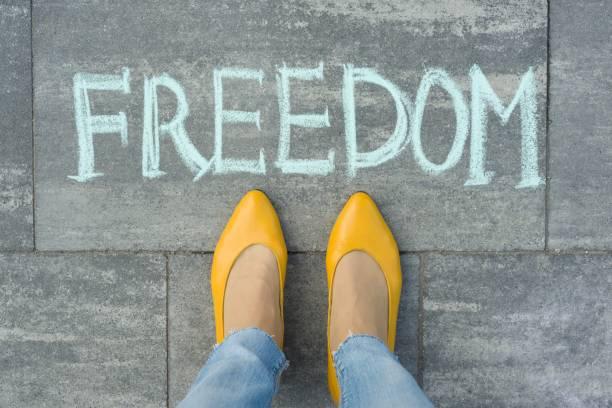 Gri kaldırım üzerine yazılmış metin özgürlüğü ile kadın ayaklar stok fotoğrafı