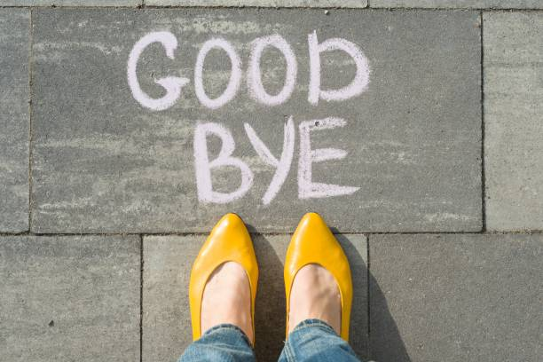 Female feet with text goodbye written on asphalt Female feet with text goodbye written on asphalt. apart stock pictures, royalty-free photos & images
