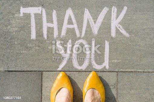 1094837778 istock photo Female feet with text thank you written on grey sidewalk 1080377164