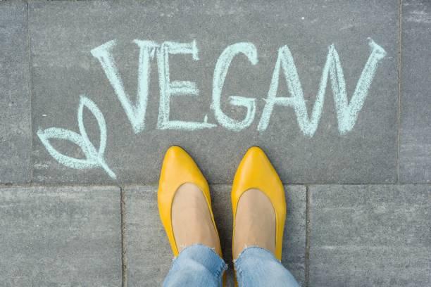 Pies femeninos con texto vegano escrito en la acera gris - foto de stock