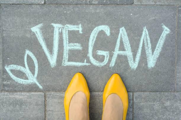 灰色の歩道に書かれたテキスト ビーガンと女性の足 - ビーガン ストックフォトと画像