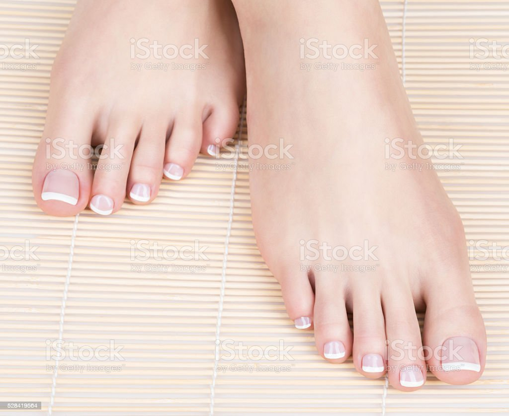 Female Feet With White French Pedicure On Nails At Spa Stock Photo ...