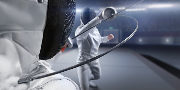 Fencing competitive duel. Female fencer fight on big professional stage. They are wearing an unbranded fencing suit.