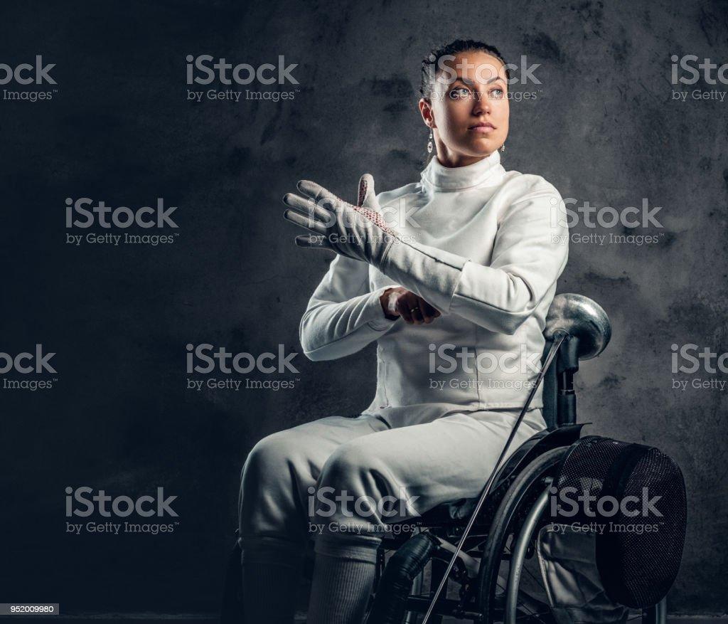 車椅子の女性剣士は、安全マスクおよび剣を保持します。 ストックフォト