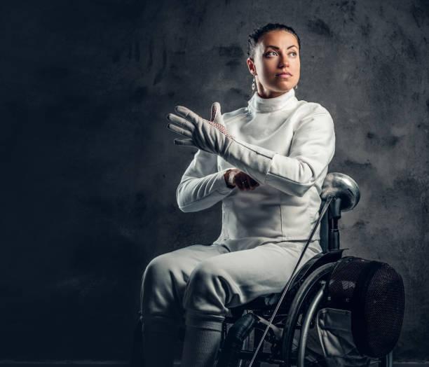 femelle escrimeur en fauteuil roulant est titulaire masque de sûreté et une épée. - sports en fauteuil roulant photos et images de collection