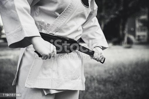 Young female fighter tightening karate belt outdoors