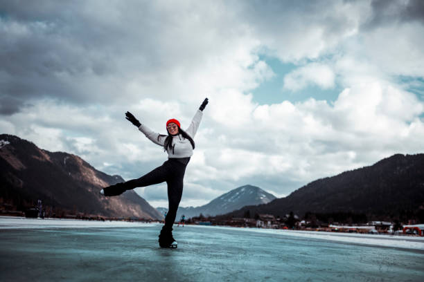 female figure skater enjoying the skating freedom on a frozen lake in winter - skate liberdade gorro imagens e fotografias de stock