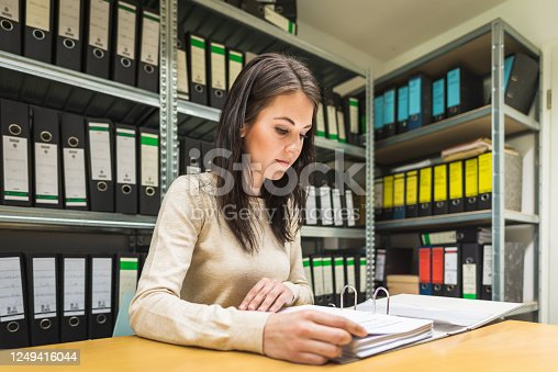 Female Business Accountant, Bookkeeper, controlling the invoices and numbers reading old financal documents in company finance file archive. Sitting at Desk in front of shelf, reading within a file folder. File Archive surrounded with ring binders, folders, files, papers in company document storage archive room.