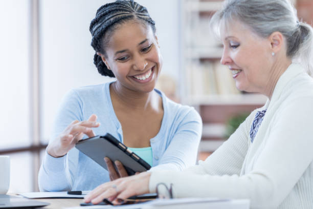Female financial advisor counsels senior client Confident African American financial advisor shows senior Caucasian female client her retirement savings. She is using a digital tablet. 40 kilometre stock pictures, royalty-free photos & images