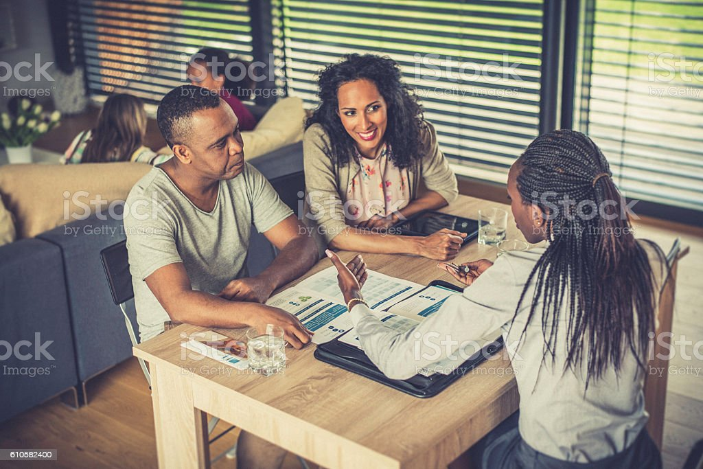 Female financial advisor talking to a couple at home stock photo