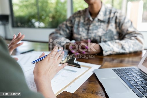 Unrecognizable female loan officer or financial advisor gestures during meeting with female military veteran.