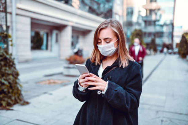 Female Finding Her Way On GPS While Wearing Anti Air Pollution Mask stock photo
