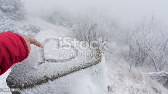Hand in red sleeve and symbol of love with frosty winter landscape in background