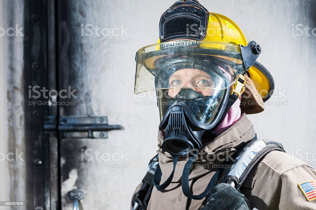 Female firefighter in protective gear and oxygen mask stock photo
