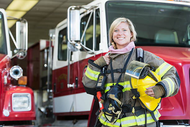 female firefighter standing in front of fire truck - firefighter stock photos and pictures