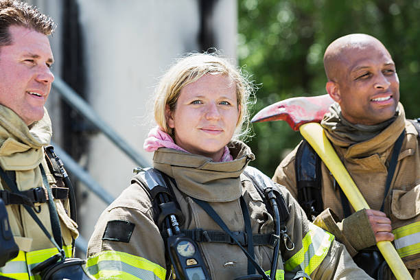 Female firefighter with two male colleagues stock photo