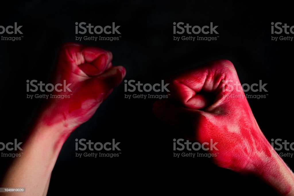 female fists in blood on black background stock photo