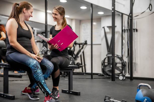 frauen fitness-trainer gehen durch schriftliche trainingsprogramm mit dem klienten - trainingstagebuch stock-fotos und bilder