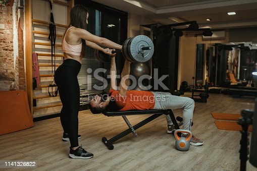 610237160istockphoto Female fitness instructor helping young man in the gym 1141326822