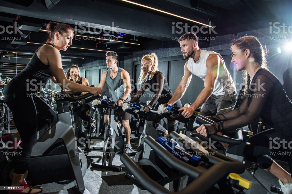 Female fitness instructor leading exercising class in gym. stock photo