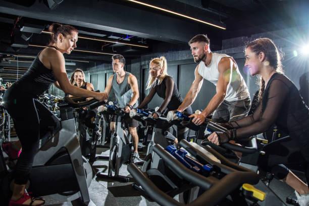 frauen fitness-instruktor führende spinning-kurs im fitness-studio. - herumwirbeln frau stock-fotos und bilder