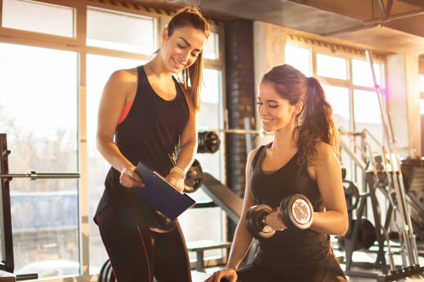female fitness instructor showing exercise progress on clipboard to young athletic woman at gym. - allenatore foto e immagini stock
