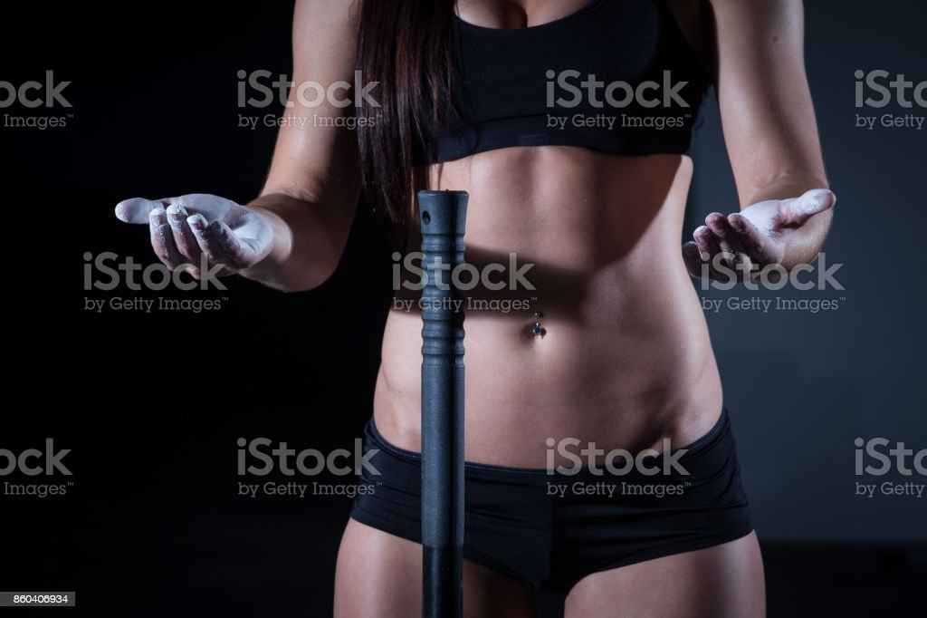 Female fitness model clapping hands with talc powder in a gym. stock photo