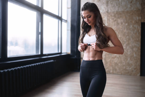 Female fitness model in white top and black leggings is posing near the big windows in studio in morning time Female fitness model in white top and black leggings is posing near the big windows in studio in morning time abdominal muscle stock pictures, royalty-free photos & images