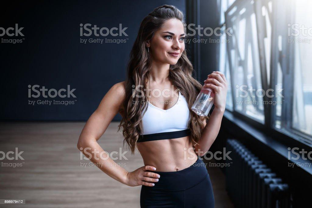 Female fitness model in white top and black leggings is posing near the big windows in studio in morning time stock photo