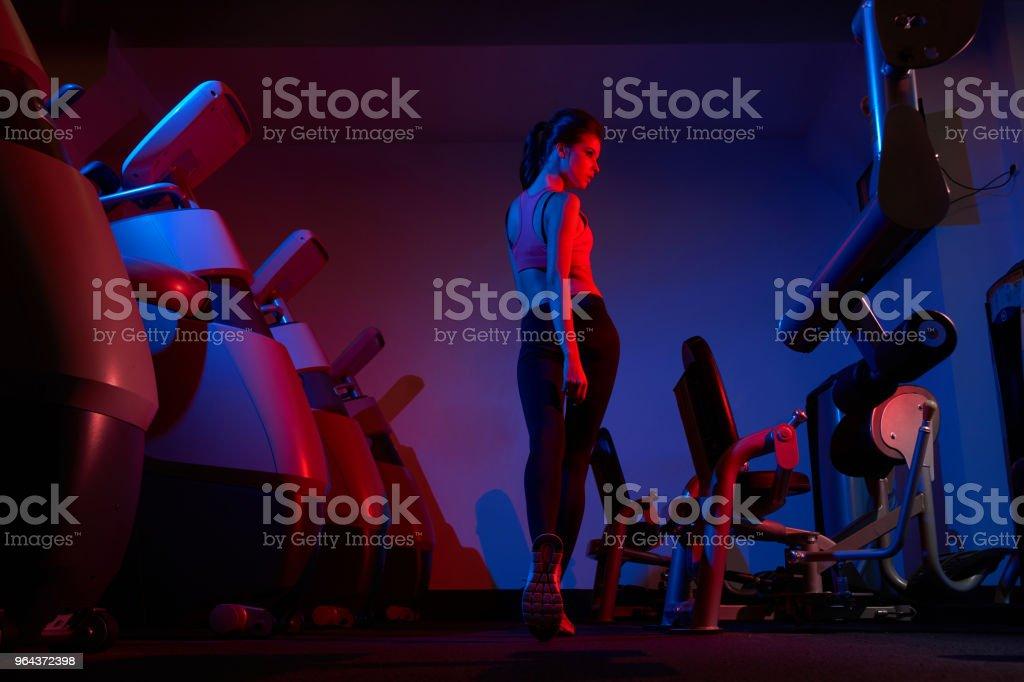 Vrouwelijke fitness model lopen tussen twee rijen van oefening machin - Royalty-free Alleen volwassenen Stockfoto