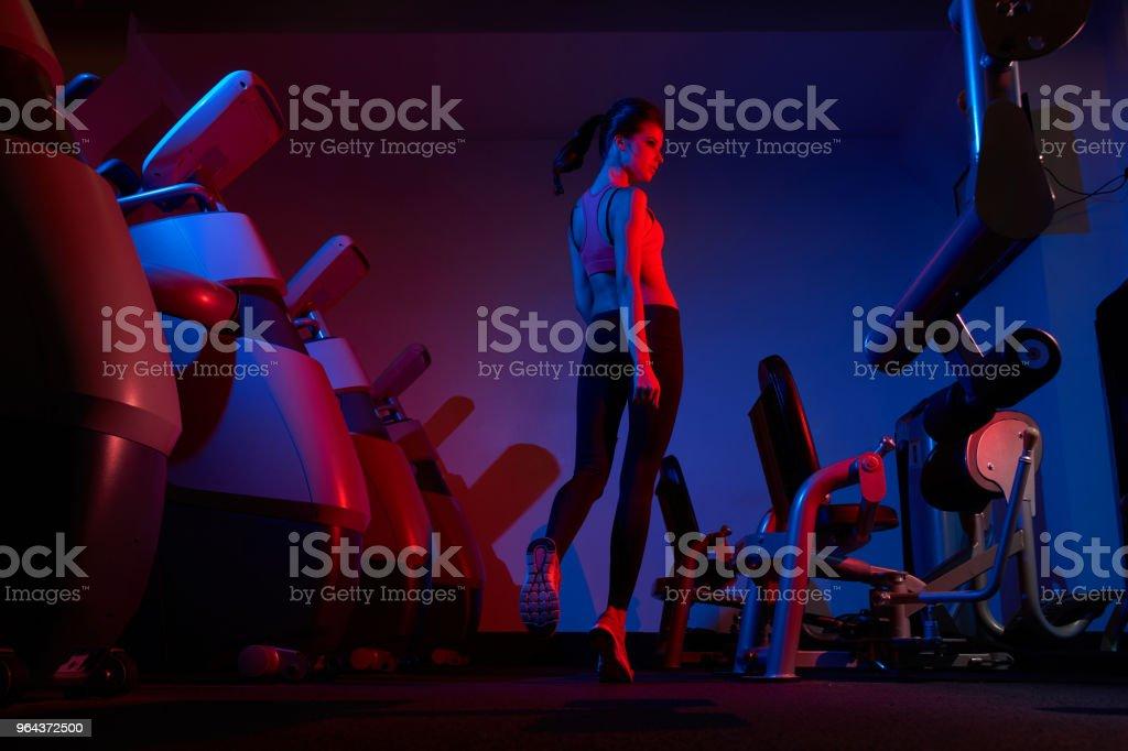 Modelo de fitness feminino andando entre duas fileiras de exercício machin - Foto de stock de Adulto royalty-free